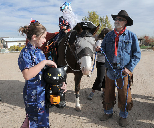 Caleigh Brown, 11, dressed in costume to hand out candy to Jack Kleinhelter, 6, riding Stuart lead by Kevin Hall and other special needs children trick or treating on horseback around the neighborhood of the Miracles Therapeutic Riding Center for Halloween on Saturday.<br /> October 30, 2010<br /> staff photo/David R. Jennings