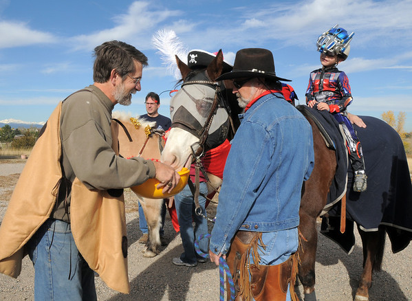 Russ Faust, left, hands out  treats to therapeutic horse Stuart lead by Kevin Hall and candy to Jack Kleinhelter, 6, dressed as a Transformer, while trick or treating on horseback in the neighborhood of the Miracles Therapeutic Riding Center for Halloween on Saturday. <br /> October 30, 2010<br /> staff photo/David R. Jennings