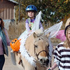 Alexandrea Waugh, 3, dressed as Tinkerbell, with her mother Becky, left, at her side, rides Folley a therapeutic horse lead by Taylor Abfalter, 15, as they trick or treat on horseback around the neighborhood of the Miracles Therapeutic Riding Center for Halloween on Saturday.<br /> October 30, 2010<br /> staff photo/David R. Jennings