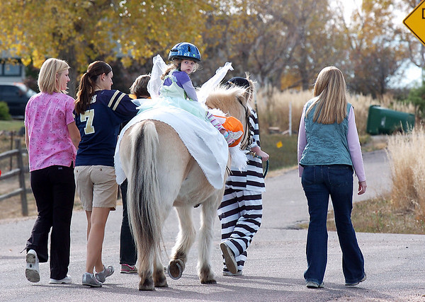 Alexandrea Waugh, 3, dressed as Tinkerbell, looks back while riding Folley a therapeutic horse lead by Taylor Abfalter, 15, as they trick or treat on horseback around the neighborhood of the Miracles Therapeutic Riding Center for Halloween on Saturday.<br /> October 30, 2010<br /> staff photo/David R. Jennings