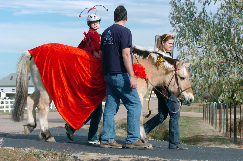 Ellena Kuhns, 3, with her parents Robin and Rich at her side, rides the Vanna, a therapeutic horse lead by Elizabeth Miller, 17, as they trick or treat on horseback around the neighborhood of the Miracles Therapeutic Riding Center for Halloween on Saturday. <br /> October 30, 2010<br /> staff photo/David R. Jennings