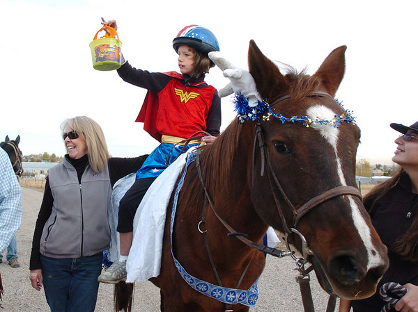 Anna Jager, 10, holds up her candy bucket  while trick or treating on horseback around the neighborhood of the Miracles Therapeutic Riding Center for Halloween on Saturday.<br /> October 30, 2010<br /> staff photo/David R. Jennings