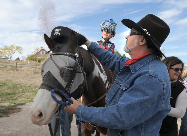 Jack Kleinhelter, 6, watches Kevin Hall adjust therapeutic horse Stuart's costume as they trick or treat on horseback around the neighborhood of the Miracles Therapeutic Riding Center for Halloween on Saturday.<br /> October 30, 2010<br /> staff photo/David R. Jennings