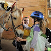 Alexandrea Waugh, 3, pets Vanna a therapeutic horse while Elizabeth Miller, 17, and Erica Seberino, 17, watch before they trick or treat on horseback around the neighborhood of the Miracles Therapeutic Riding Center for Halloween on Saturday.<br /> October 30, 2010<br /> staff photo/David R. Jennings