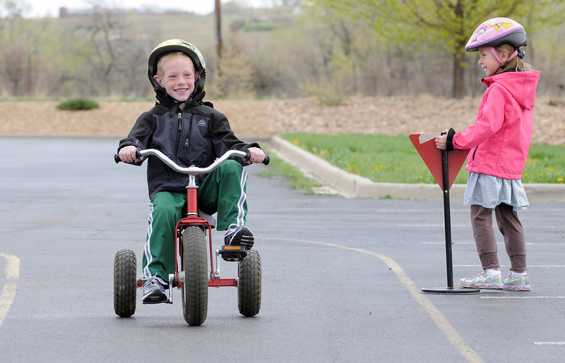 Bryce Newham, left, is all smiles while passing by fellow kindergartener Olivia Thomas standing next to a yield sign during the Cross of Christ Preschool  Trike-a-Thon on Thursday as a fundraiser for St. Jude Children's Hospital.<br /> <br /> <br /> April 12, 2012 <br /> staff photo/ David R. Jennings
