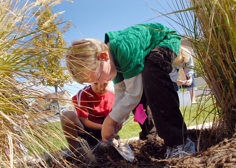 Andrew Blanchette, right, and Spencer Schauman dig a hole for tulips as theMeridian Elementary first graders help plant some of the more than 500 tulips of four different varieties at the school on Friday. October 8, 2010<br /> staff photo/David R. Jennings