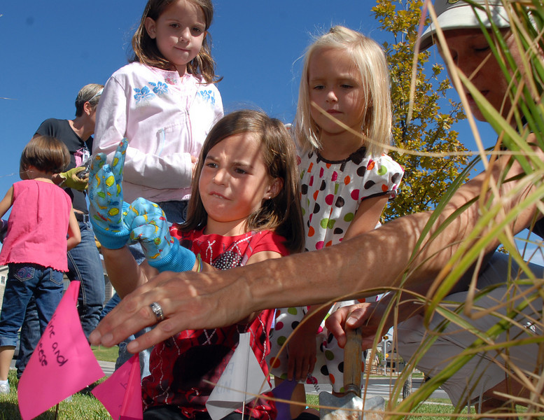 Meridian Elementary first grade Delaney Rutligiano puts on her gardening gloves to help  Haley Gallagher plant tulips of four different varieties at the school on Friday. <br /> October 8, 2010<br /> staff photo/David R. Jennings