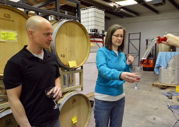 Kristina Crain, right, and her husband Martin take a sample Turquoise Mesa Winery wine from a barrel during the Turquoise Mesa Winery wine club tasting event on Saturday. Turquoise Mesa Winery moved to a new location at 117th Ave. and Teller St.<br /> <br /> February 2, 2013<br /> staff photo/ David R. Jennings