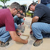 Scott Shipman, left, Ty Morian and Jerry Magnetti with Westminster Parks place an engraved brick in honor of World War II veteran Paul Murphy, survivor of the sinking of the USS Indianapolis, at the Westminster Armed Forces Tribute Garden on Thursday. <br /> <br /> July 22, 2010<br /> Staff photo/ David R. Jennings