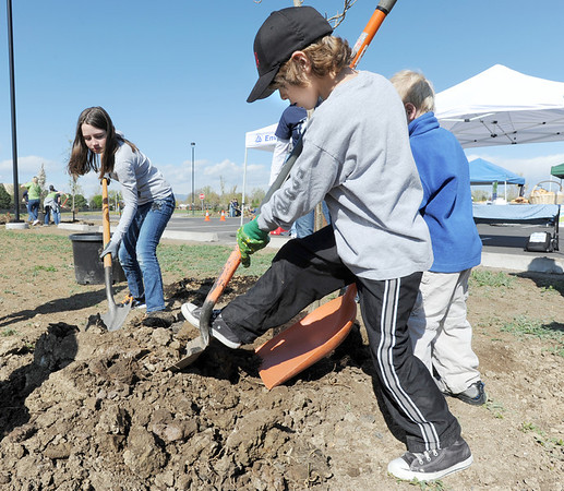 "Seth Roberts, 8, right, shovels dirt to cover a tree with Katherine Tutt, 11, left,  in the area between North Metro Fire Rescue headquarters and Mamie Doud Eisenhower Public LIbrary during the ""Trees for a Healthy Community and Economy"" event on Saturday. <br /> <br /> April 14, 2012 <br /> staff photo/ David R. Jennings"