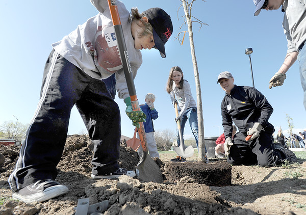 "Seth Roberts, 8, left,  helps plant a tree in the area between North Metro Fire Rescue headquarters and Mamie Doud Eisenhower Public LIbrary during the ""Trees for a Healthy Community and Economy"" event on Saturday. <br /> <br /> April 14, 2012 <br /> staff photo/ David R. Jennings"