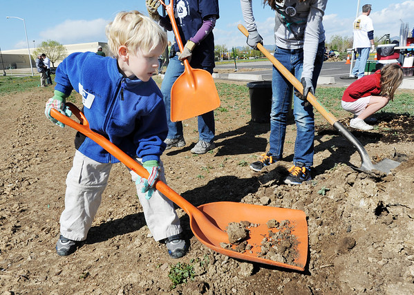 "Lyle Roberts, 6, scoops up dirt to help plant a tree in the area between North Metro Fire Rescue headquarters and Mamie Doud Eisenhower Public LIbrary during the ""Trees for a Healthy Community and Economy"" event on Saturday. <br /> <br /> April 14, 2012 <br /> staff photo/ David R. Jennings"