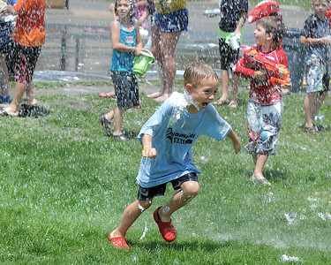 Will Nolan, 6, runs through the water sprayed by North Metro Fire Rescue firefighters during the water fight marking the last day of the Totus Tuus program at Nativity of Our Lord Church and School on Friday. June 17, 2011 staff photo/David R. Jennings