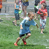 Will Nolan, 6, runs through the water sprayed by North Metro Fire Rescue firefighters during the water fight marking the last day of the Totus Tuus program at Nativity of Our Lord Church and School on Friday.<br /> June 17, 2011<br /> staff photo/David R. Jennings