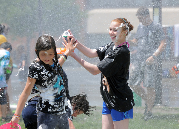 Emma Shilney, 11, squirts shaving cream on a fellow student during the water fight marking the last day of the Totus Tuus program at Nativity of Our Lord Church and School with water sprayed on the students by North Metro Fire Rescue firefighters on Friday.<br /> June 17, 2011<br /> staff photo/David R. Jennings