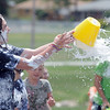 Alexa Biggerstaff, 16, throws water on children during the water fight marking the last day of the Totus Tuus program at Nativity of Our Lord Church and School on Friday.<br /> June 17, 2011<br /> staff photo/David R. Jennings