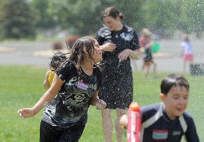 Bryn Ventura, 11, runs away from water sprayed by North Metro Fire Rescue firefighters during the water fight marking the last day of the Totus Tuus program at Nativity of Our Lord Church and School on Friday. June 17, 2011 staff photo/David R. Jennings