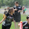Bryn Ventura, 11, runs away from water sprayed by North Metro Fire Rescue firefighters during the water fight marking the last day of the Totus Tuus program at Nativity of Our Lord Church and School on Friday.<br /> June 17, 2011<br /> staff photo/David R. Jennings