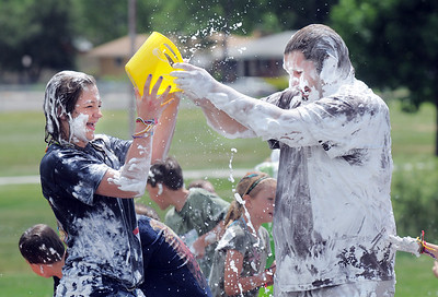 Alexa Biggerstaff, 16, left, tries to get water on Mark Thomason, director of the program, covered in shaving cream,  during the water fight marking the last day of the Totus Tuus program at Nativity of Our Lord Church and School with water from the air supplied by North Metro Fire Rescue on Friday. June 17, 2011 staff photo/David R. Jennings