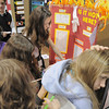 Westlake Middle School 6th graders Lexi Durnin and Cheyen Dizney, left, take notes using the back of Alyssa Bass while Carlie Preskitt, an 8th grader, explains her chemistry experiment  to determine enthalpy of thermodynamic reactions during the science fair show at the school on Thursday.<br /> April 7, 2011<br /> staff photo/David R. Jennings