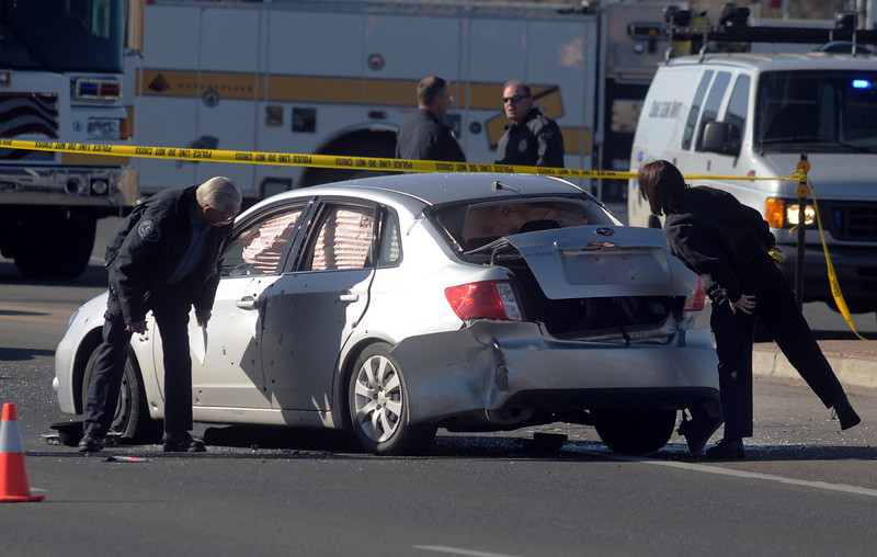 Criminalists look at the suspect's vehicle at the scene of a shoot out with Westminster Police at eastbound 120th Ave. and Federal Blvd. on Thursday.<br /> Two Westminster officers were shot in the gun battle. Federal is closed both directions from Federal Blvd. to Pecos St.<br /> November 19, 2009<br /> Staff photo/David R. Jennings