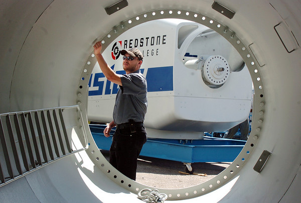 Redstone College student Michael Decker checks the 40 foot tall base for the 18,200 lb. Vestas V27 wind turbine head, in the background, which was delivered to the school on Thursday.  The college is planning on launching a new Wind Energy Technology Program later this summer. The wind turbine and base will be used for hands-on training. <br /> <br /> June 10, 2010<br /> Staff photo/ David R. Jennings