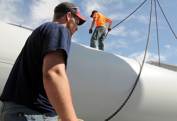 Redstone College student Brian Key, left, helps crane operator Jesse Coffman with Boulder Valley Crane Service, in preparing to move the base for the Vestas V27 wind turbine head at the school on Thursday.  The college is planning on launching a new Wind Energy Technology Program later this summer. The wind turbine will be used for hands-on training.<br /> <br /> June 10, 2010<br /> Staff photo/ David R. Jennings