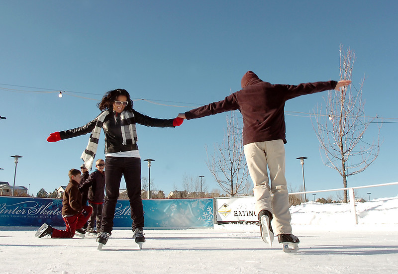 Anisha Mathi, from Tennesee, ice skates with Johnny Hodgson, from Boulder, at the  Winter Skate ice rink  at the FlatIron Crossing mall on Friday.<br /> <br /> December 23, 2011<br /> staff photo/ David R. Jennings