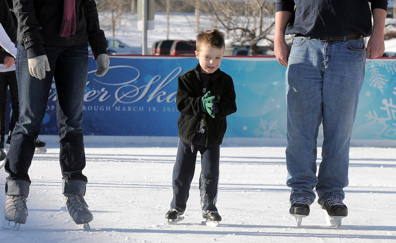 Jack Cooney, 4 skates with his parents Jenn and Sean, from Thornton,  at the  Winter Skate ice rink  at the FlatIron Crossing mall on Friday.<br /> <br /> December 23, 2011<br /> staff photo/ David R. Jennings
