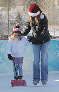 Brynne Paterson, 6, left, holds a snow shovel while skating with her mother Shelley at the Winter Skate ice rink  at the FlatIron Crossing mall on Friday.  December 23, 2011 staff photo/ David R. Jennings