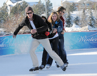 Johnny Hodgson, left, leads Anisha Mathi, Annie Hodgson, 15, Taylor Balthazor and Daniel Hodgson skate in a line at the  Winter Skate ice rink  at the FlatIron Crossing mall on Friday.  December 23, 2011 staff photo/ David R. Jennings