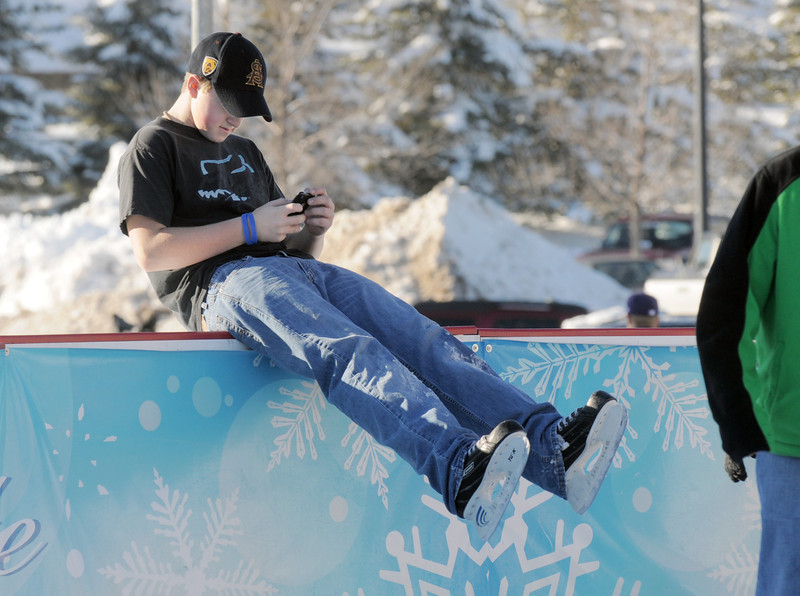 Kyler Paterson, 14, stops to check his phone while ice skating at the  Winter Skate ice rink  rink at the FlatIron Crossing mall on Friday.<br /> <br /> December 23, 2011<br /> staff photo/ David R. Jennings