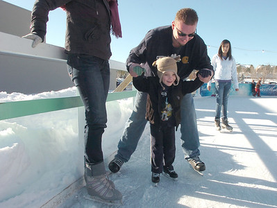 Sean Cooney steadies his son Jack, 4, while ice skating at the  Winter Skate ice rink  at the FlatIron Crossing mall on Friday.  December 23, 2011 staff photo/ David R. Jennings