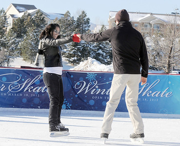 Anisha Mathi, left, from Tennesee, skates with Johnny Hodgson at the  Winter Skate ice rink  at the FlatIron Crossing mall on Friday.  December 23, 2011 staff photo/ David R. Jennings