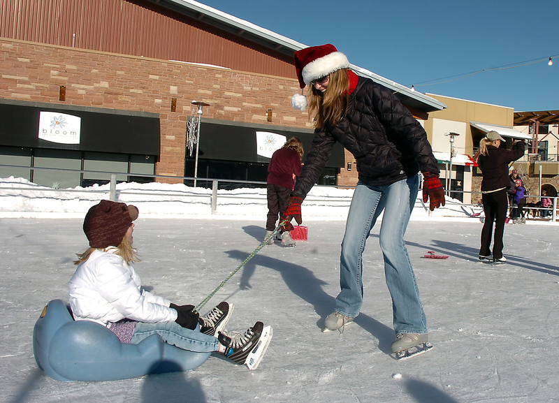 Shelley Paterson, right, pulls her daughter Brynne, 6, at the  Winter Skate ice rink  at the FlatIron Crossing mall on Friday. The Paterson family came from Windsor to skate at the rink.<br /> <br /> December 23, 2011<br /> staff photo/ David R. Jennings