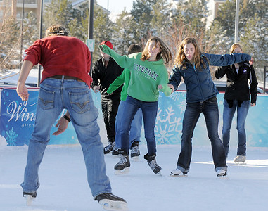 Annie Hodgson, 15, center, and Taylor Balthazor skate towards Daniel Hodgson at the Winter Skate ice rink  at the FlatIron Crossing mall on Friday.  December 23, 2011 staff photo/ David R. Jennings