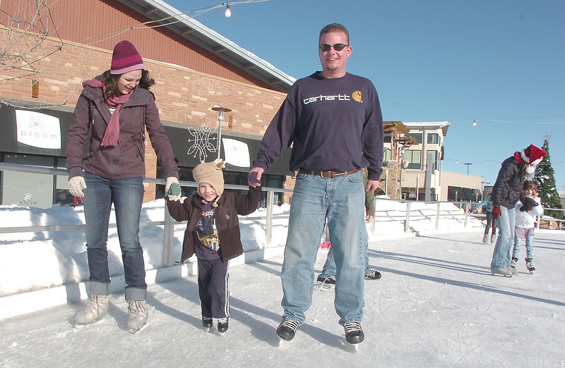 Jenn Cooney, left, and her husband Sean, right, skates with their son Jack, 4, at the Winter Skate ice rink  at the FlatIron Crossing mall on Friday.<br /> <br /> December 23, 2011<br /> staff photo/ David R. Jennings