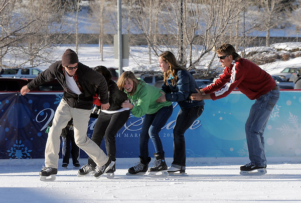 Johnny Hodgson, left, leads Anisha Mathi, Annie Hodgson, 15, Taylor Balthazor and Daniel Hodgson skate in a line at the Winter Skate ice rink at the FlatIron Crossing mall on Friday.<br /> <br /> December 23, 2011<br /> staff photo/ David R. Jennings