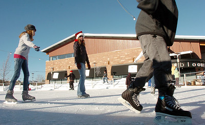 Kailey Paterson, 12, left, skates with her mother Shelley, center, at the  Winter Skate ice rink at the FlatIron Crossing mall on Friday.  December 23, 2011 staff photo/ David R. Jennings