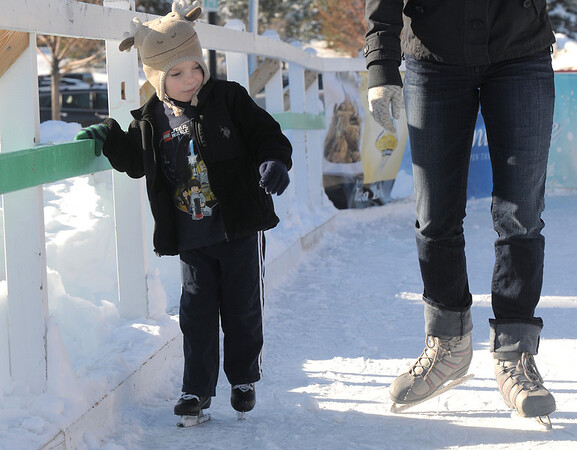 Jack Cooney, 4, hangs onto the side rail as he skates with his mother Jenn at the Winter Skate ice rink  at the FlatIron Crossing mall on Friday.<br /> <br /> December 23, 2011<br /> staff photo/ David R. Jennings