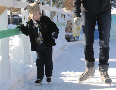 Jack Cooney, 4, hangs onto the side rail as he skates with his mother Jenn at the Winter Skate ice rink  at the FlatIron Crossing mall on Friday.  December 23, 2011 staff photo/ David R. Jennings