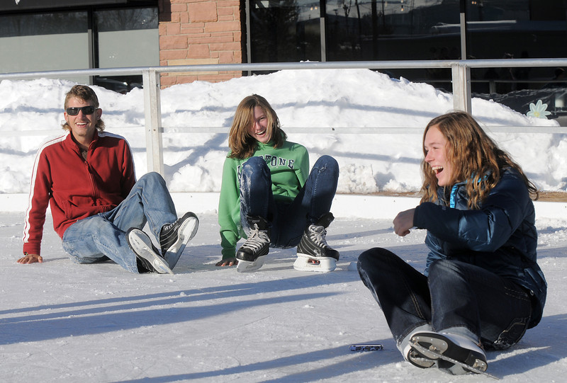 Daniel Hodgson, left, Annie Hodgson, 15, laugh with Taylor Balthazor after falling while ice skating at the Winter Skate ice rink  at the FlatIron Crossing mall on Friday.<br /> <br /> December 23, 2011<br /> staff photo/ David R. Jennings