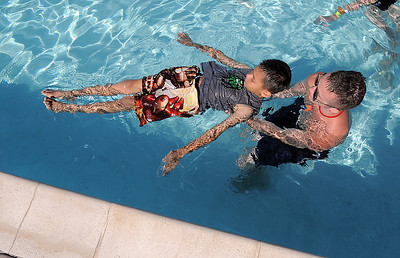Life guard instructor Eli Davis helps beginning swimmer Alex Rodriguez, 8, float during the World's Largest Swimming Lesson sponsored by the Kiwanis at the Bay Aquatic Center on Tuesday. June 14, 2011 staff photo/David R. Jennings