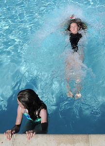 Anna Barjenbruch, 11, right, pushes off the edge of the pool while Marlow Anderson, 8, waits her turn during the World's Largest Swimming Lesson sponsored by the Kiwanis at the Bay Aquatic Center on Tuesday. June 14, 2011 staff photo/David R. Jennings