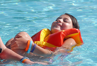 Victoria Ruelas, 10, floats with a life jacket during the World's Largest Swimming Lesson sponsored by the Kiwanis at the Bay Aquatic Center on Tuesday. June 14, 2011 staff photo/David R. Jennings