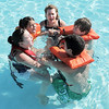 Instructor Holly Dahm, center, huddles with, from left, Victoria Ruelas, 10, left, Annemarie Abeyta, 10, Brock Abeyta, 13, and Forest Garrigan, 13, as the group learns to call for help if stranded in the water during the World's Largest Swimming Lesson sponsored by the Kiwanis at the Bay Aquatic Center on Tuesday.  <br /> June 14, 2011<br /> staff photo/David R. Jennings