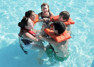 Instructor Holly Dahm, center, huddles with, from left, Victoria Ruelas, 10, left, Annemarie Abeyta, 10, Brock Abeyta, 13, and Forest Garrigan, 13, as the group learns to call for help if stranded in the water during the World's Largest Swimming Lesson sponsored by the Kiwanis at the Bay Aquatic Center on Tuesday.   June 14, 2011 staff photo/David R. Jennings