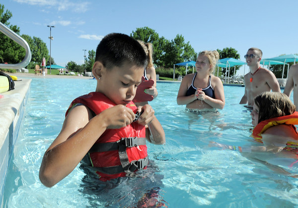 Alex Rodriguez, 8, puts on a life jacket during the World's Largest Swimming Lesson sponsored by the Kiwanis at the Bay Aquatic Center on Tuesday.<br /> June 14, 2011<br /> staff photo/David R. Jennings