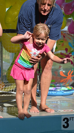 Instructor Liz Kaplan helps Kathleen Schoonveld, 3, with safely jumping into the pool  during the World's Largest Swim Lesson at the Broomfield Academy on Thursday.<br /> <br /> June 14, 2012 <br /> staff photo/ David R. Jennings