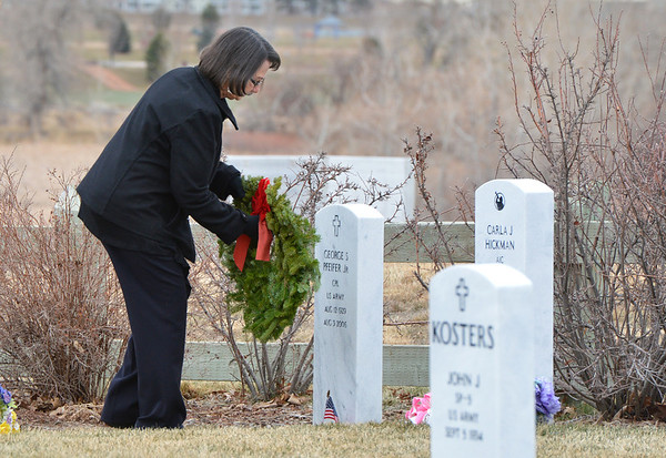 Edna Pfeifer places a holiday wreath on the grave of her husband, US Army veteran, George Pfeifer Jr. on Saturday at the Broomfield County Commons Cemetery for the Wreaths Across America. The Broomfield Rotary Club sponsored event placed wreaths on the graves of veterans at three cemeteries simultaneously.<br /> December 14, 2012<br /> staff photo/ David R. Jennings